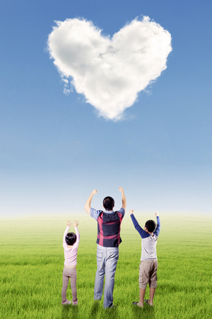 under heart: Picture of happy father and his children raise hands together on the meadow under cloud shaped heart symbol