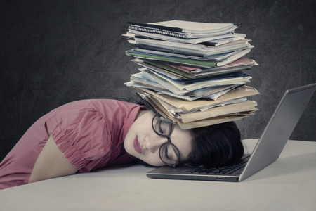 stressful: Photo of a stressful young businesswoman sleeping over a laptop with a stack of documents on her head