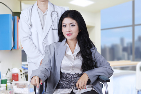 asian adult: Beautiful woman with long hair, sitting on the wheelchair with her doctor in the hospital room