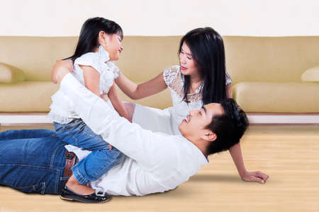 dad and daughter: Portrait of cheerful Asian family having fun and laughing together on the floor at home