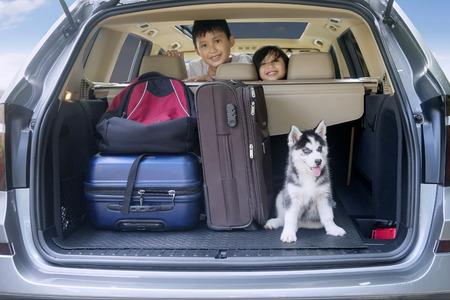 Twee vrolijke kinderen glimlachen in een auto met husky hond en bagage voor op reis