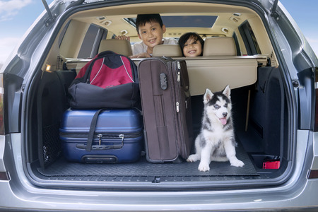 street love: Two cheerful children smiling inside a car with husky dog and luggage for traveling