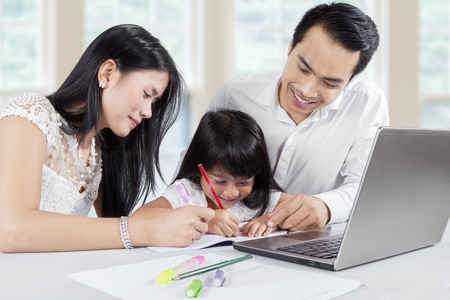 Two young Asian parents teach their daughter to write and doing homework with a laptop on desk at home Stock Photo