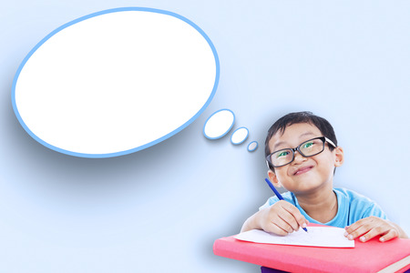speech: Image of male elementary school student studying and writes on the paper with empty speech bubble