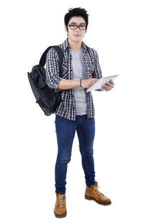 MOCHILA: Estudiante asiático masculino bolsa de transporte y que usa la tableta digital en el estudio, aislado en fondo blanco Foto de archivo