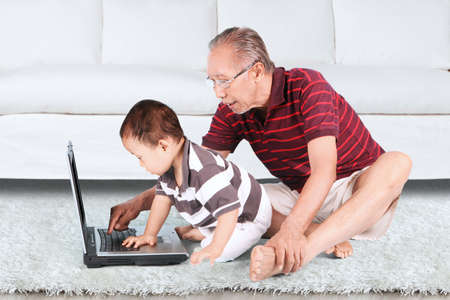 grandfather and grandson: Portrait of grandfather and baby boy using a laptop together while sitting on carpet Stock Photo
