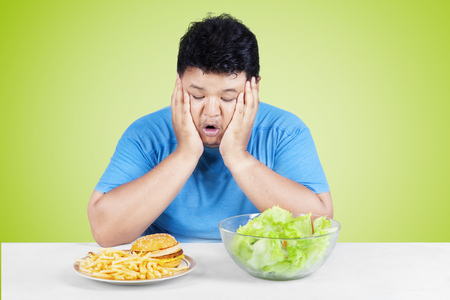 asian guy: Picture of overweight person looking at salad and hamburger, looks confused to choose it