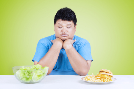 choose person: Overweight person looks confused to choose salad or hamburger on the table Stock Photo