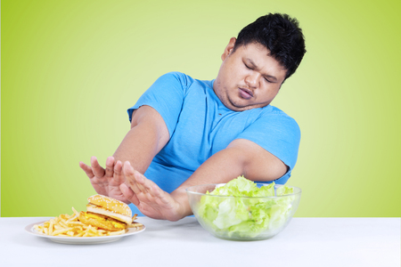 refuse: Portrait of an overweight person refuse to eat a plate of junk food on the table Stock Photo