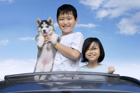 sunroof: Happy Asian children standing on the sunroof of the car while holding siberian husky puppy and smiling at the camera Stock Photo