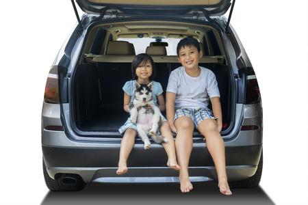 gente sentada: Retrato de dos niños alegres que se sientan en el coche con el perro ronca y sonriendo a la cámara, aislado en fondo blanco Foto de archivo