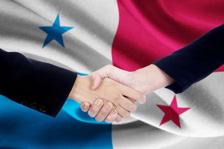 bandera panama: Dos manos de los trabajadores el cierre de una reuni�n dando la mano delante de una bandera de Panam� Foto de archivo