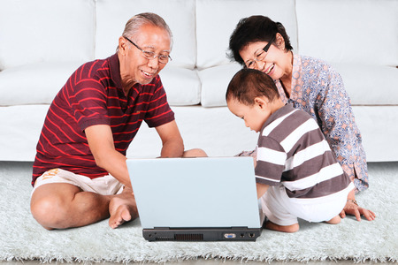 chinese lady: Baby learn how to use a laptop with grandpa and grandma while sitting on carpet Stock Photo