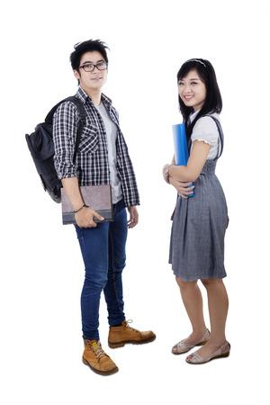 mujeres de espalda: Retrato de dos estudiantes universitarios asiáticos pie en el estudio y sonriendo a la cámara, aislado en fondo blanco Foto de archivo