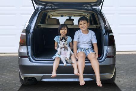 2 人の幸せな子供持株ハスキー犬中の車に座って、カメラで笑顔の写真