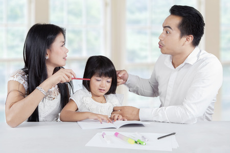 man scolding: Picture of two young parents quarreling at home while their daughter listening and crying
