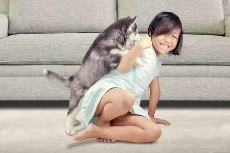 gente sentada: Retrato de una niña alegre que se divierte con cachorro de husky siberiano en el suelo en el país