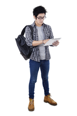 asian adult: Image of male high school student using a digital tablet computer while standing in the studio, isolated on white background