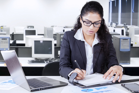 hispanic woman: Photo of a young businesswoman writes a journal in the office while working with a laptop on desk Stock Photo