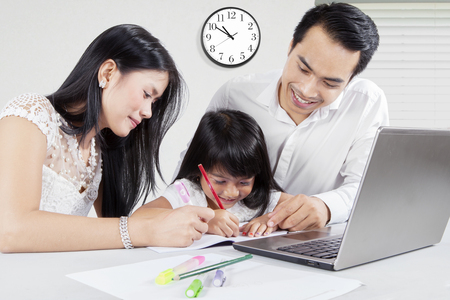 Young Asian man and his wife teach their daughter to study and write on the book with a laptop on desk