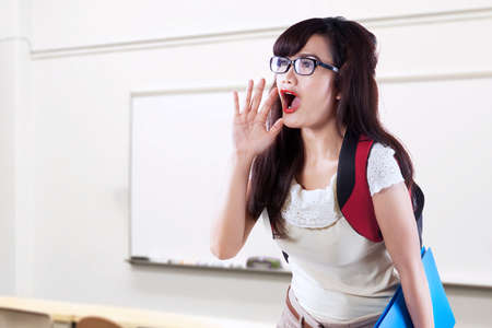 squeal: Female high school student with long hair and wearing glasses, screaming in the classroom Stock Photo