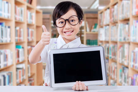 thumbs: Picture of a cute female elementary school student holding tablet and showing thumb up in the library Stock Photo