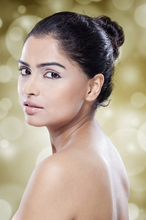 cabello negro: Retrato de la hermosa mujer india con el pelo negro, cara preciosa, y la piel perfecta mirando a la cámara contra el fondo del bokeh Foto de archivo