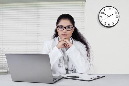 Portret van de Indiase vrouwelijke arts zitten in het kantoor en kijkt vol vertrouwen met een laptop op het bureau