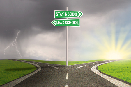risks ahead: Image of empty highway with two choices on the signpost to stay or leave school