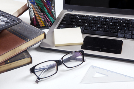 Close up of a glasses on the table with laptop, books, ruler, calculator, and stationery