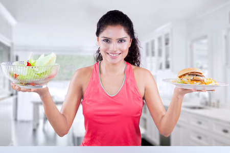 comparing: Picture of healthy woman comparing a bowl of fresh salad and a plate of hamburger in the kitchen