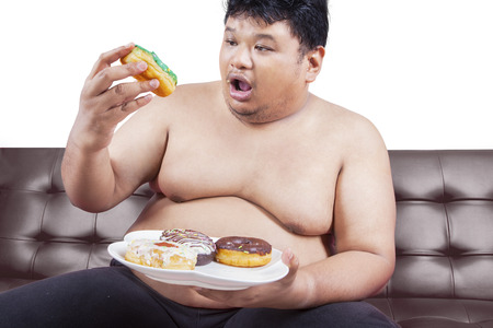 young male: Picture of a young obese man sitting on brown sofa and enjoy donuts, isolated on white background