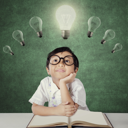 Photo of a little girl sitting in the classroom while daydreaming under lightbulb with a book on the table