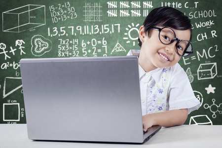 homework student: Sweet little student smiling at camera and using laptop computer in the class Stock Photo