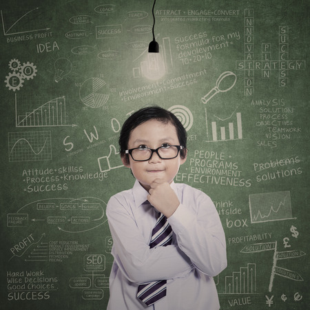 lit: Business kid is thinking under lit bulb in class full of drawn formula