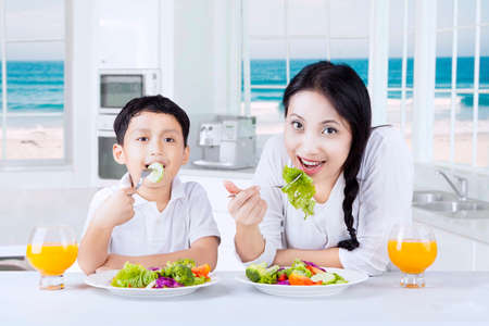 mom son: Portrait of a little boy and his mother sitting in the kitchen while enjoy vegetables salad and drink orange juice