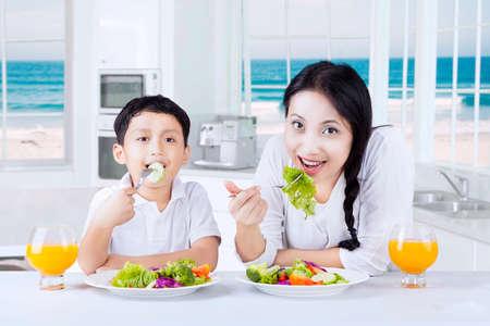 mama e hijo: Retrato de un niño pequeño y su madre sentada en la cocina mientras disfrutar de ensalada de verduras y beber jugo de naranja Foto de archivo
