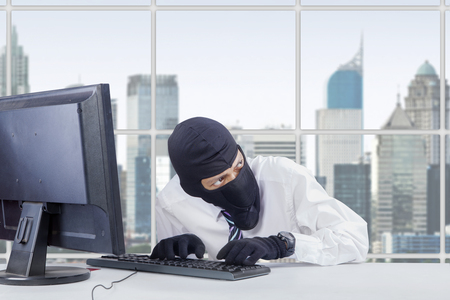 watchful: Picture of watchful thief wearing mask while stealing information on the computer in office