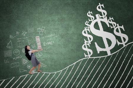 Élève du secondaire portant des livres pour apprendre avec le symbole de la monnaie du dollar sur le tableau noir