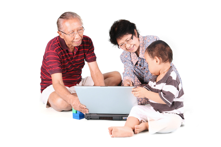 teach: Grandparents with their grandson using a laptop and sitting in studio Stock Photo