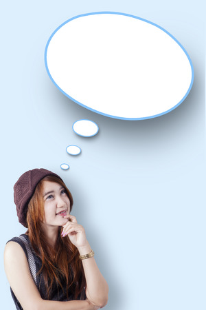 dialogo: Retrato de una adolescente que mira un bocadillo en blanco en el estudio