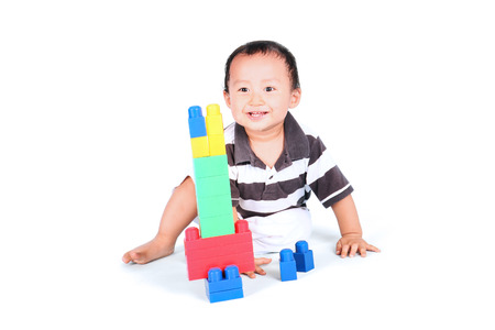 baby toys: Baby playing with colourful blocks and sitting in studio, isolated on white background Stock Photo