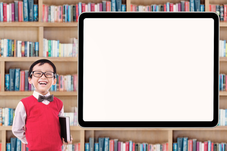 elementary school: Cute male elementary school student standing in the library while laughing near the whiteboard Stock Photo