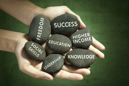 staying: Image of hands holding stones with aim of education written on it