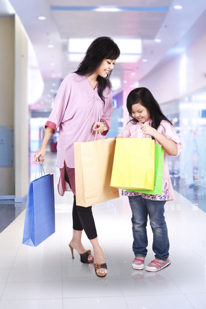 Cheerful mother and her daughter carrying shopping bags in the mall photo
