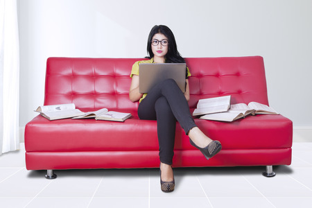 using computer: Photo of a pretty young woman sitting on the sofa while using laptop computer with books