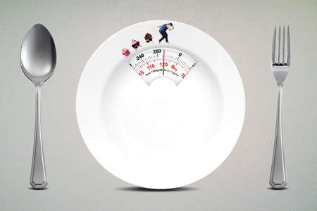 obese man: Diet concept. Overweight person runs on empty plate shaped a scale with a spoon and fork
