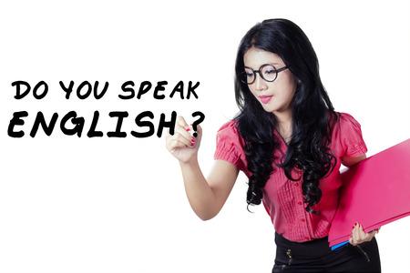 asian teacher: Young Asian teacher writes Do You Speak English on the whiteboard, isolated on white background
