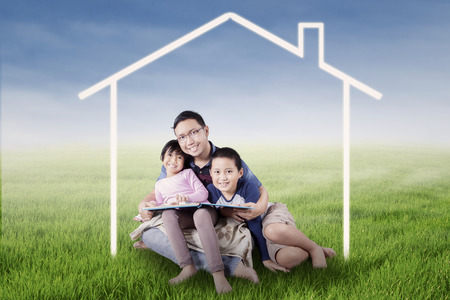 house family: Photo of two happy children and their father smiling at the camera while sitting under a house symbol on the meadow Stock Photo