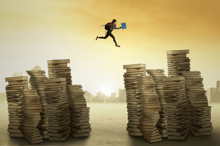 adult student: Picture of a female college student carrying bag and jumping over the pile of books Stock Photo